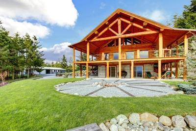 wood frame architectural home with landscaping and grass